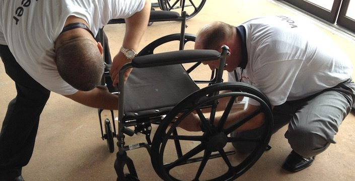 Two men building a wheelchair