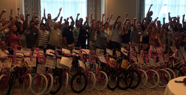 Big team cheering with their completed bike build donations