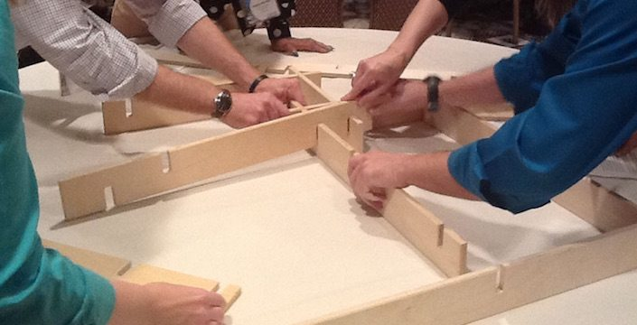 Team working with each other to put a wooden puzzle together