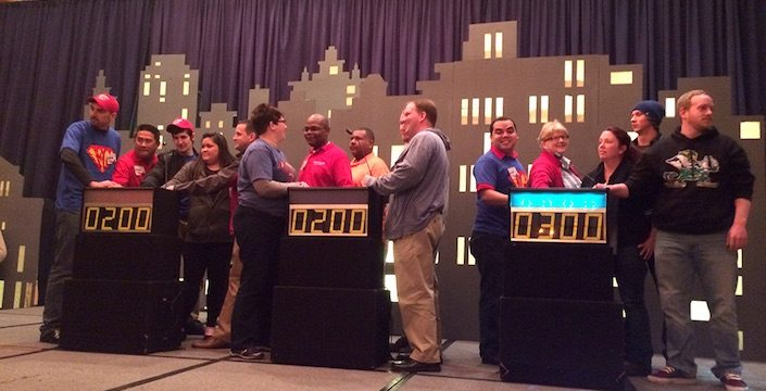 Teams standing at podiums getting ready to play a game show