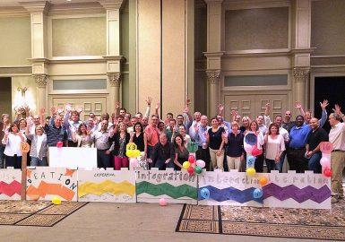 Large group inside a hotel ballroom cheering as they stand behind their completed bridge build