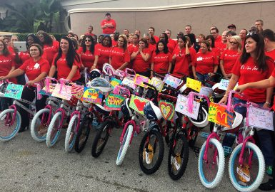 Large team wearing red shirts with their built and decorated bikes
