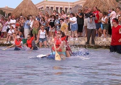 Build-a-Raft Competition participants racing rafts as their team cheers them on from behind