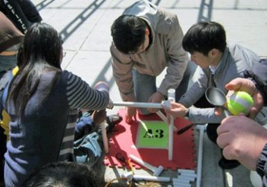 Catapult team outside building their catapult