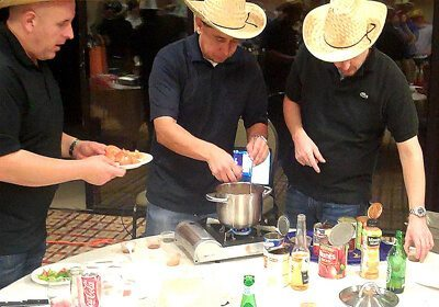 Three guys standing around a table working on Chili Cook-Off program
