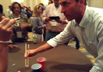 Action shot of man playing chopsticks activity at a table