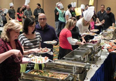 Participants serving themselves from multiple hot food trays