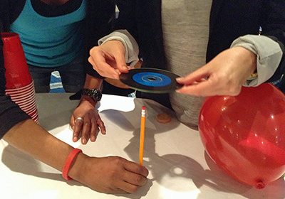Participants dropping a CD through a standing up pencil