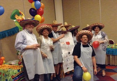 Teammates posing for a picture dressed in aprons and sombreros holding their written out slogan