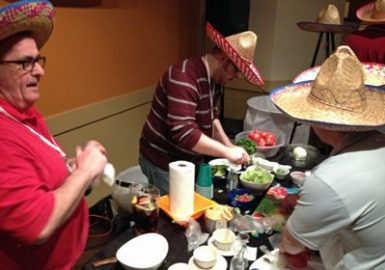 Participants with sombreros preparing a food on a table