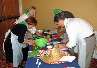 Teammates prepping their Fiesta Fun!™ dishes at their table with a sombrero on it