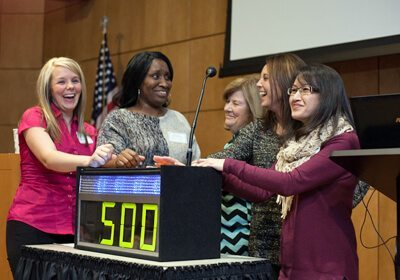 Picture of team laughing together at podium during Game Show Mania