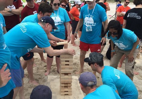 Picture of team playing Jenga on the beach during Let the Games Begin program