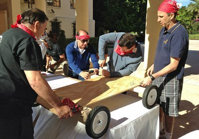 Go-Kart Competition team with red bandanas building their cart on a table