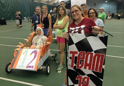 Go-Kart Competition team pushing their custom cart and driver to the starting line