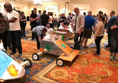 Go-Kart teams lining up to race inside a hotel ballroom
