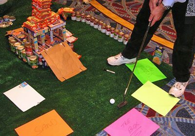Teammate putting up a slope made of cardboard during their Charity Mini-Golf Course Build