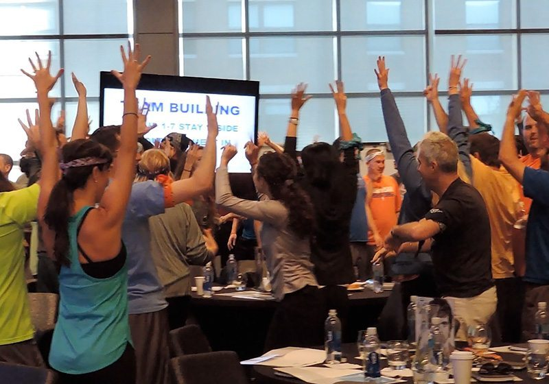 Picture of team with hands up during Igniting Team Performance program