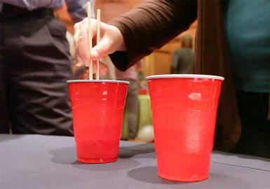 Female participant using chopsticks to put an item into a red cup