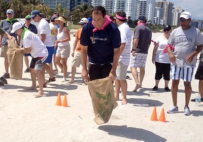 Picture of a sack race at the beach during Let the Games Begin program