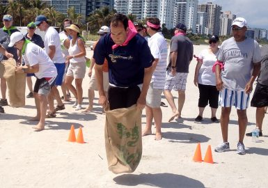 Teammate doing the Sack Race on the beach