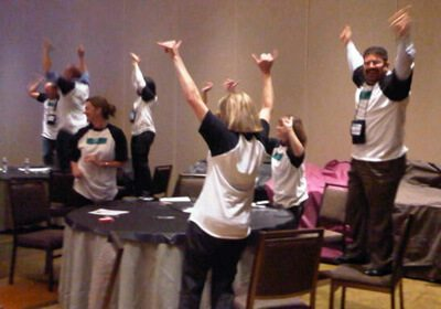 Speed Networking team standing around a table with their hands in the air