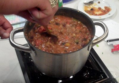 A hand stirring a pot of chili