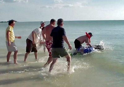 Build-a-Raft Competition action shot of team members pushing their raft off the beach and into the ocean