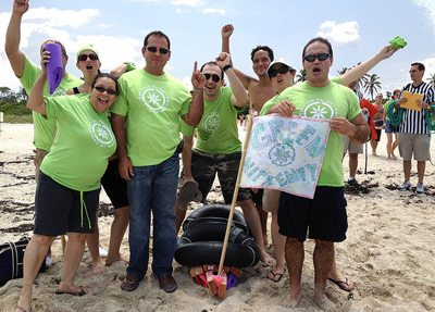 Build-a-Raft Competition group with green t-shirsts striking a pose on the beach with their team flag