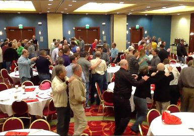 Teams doing a conga line in a hotel ballroom
