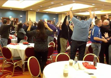 Teams in a hotel ballroom with their arms up cheering