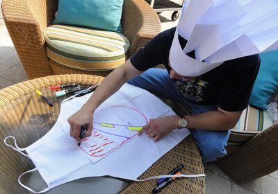 Participant drawing his team design on his apron
