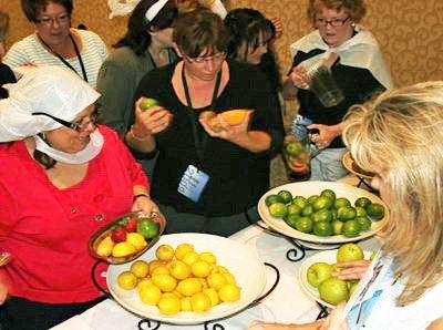 Participants standing around a white table with two large bowls of lemons and limes