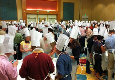 Hotel ballroom filled with people at various tables wearing chef hats