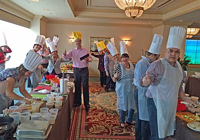 Picture of participants in chef outfits posing around their tables