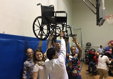 Team holds finished wheelchair aloft