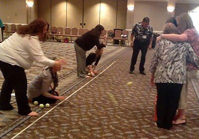 Competition to Collaboration team bounces balls over a tape line