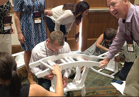 Team holding white rocking horse upside while they assemble it