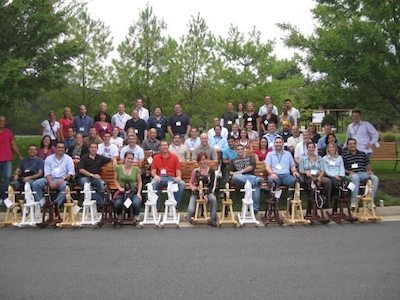 Large team posing outside with all their completed rocking horses up front