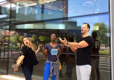 Amazing Chase team pretending to sing as they stand in front of the Dallas Opera House