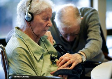 Alzheimer's patient sitting with her eyes closed listening to music while a man beside her holds her hand