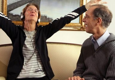 Elderly woman with headphones holding her arms in the air listening to music