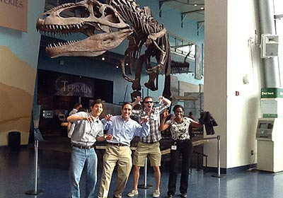 Amazing Chase SmartHunt action shot of participants at a museum posing in front of a dinosaur exhibit.