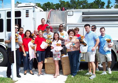 participants posing with their finished bears and blankets in front of a firetruck
