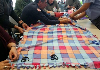 Team making a knot blanket