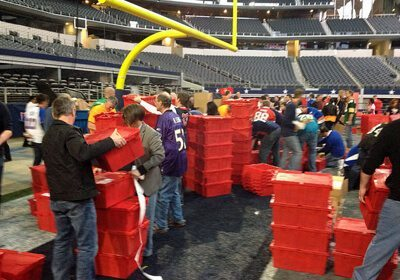 Participants assembling their Donation Nation™ Care Packs on the floor of a football stadium