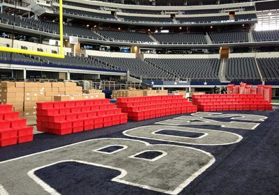 Completed Donation Nation™ Care Packs boxes organized in rows on the floor of the Dallas Cowboys football stadium