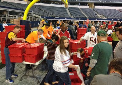Teams working on their Donation Nation™ Care Packs on the floor of a football stadium