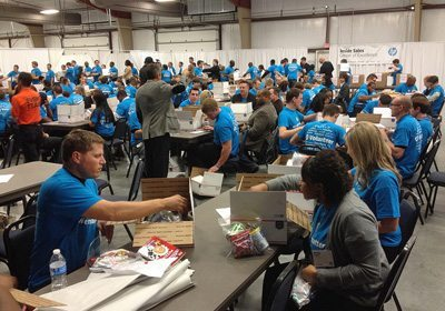Room full of participants in blue shirts building their Donation Nation™ Care Packs