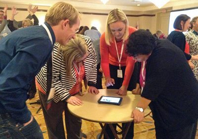 Picture of participants gathered around a little table with an iPad in the middle